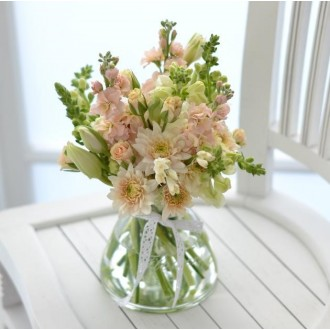 Vintage style posy of pastel flowers in glass vase